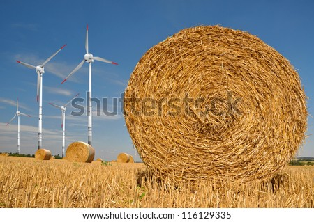 Straw bales on farmland with wind turbine on blue cloudy sky