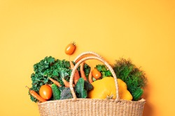 Straw basket with organic vegetables over trendy yellow background. Healthy food, vegetarian diet. Eco friendly, zero waste, plastic free concept