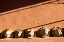 Straw beach hats standing on terracotta  clay wall.  Bright sunlight and hard shadows.