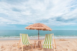 Straw beach rattan parasol with green beach chairs at the beach with blue sky backgrounds. Relax at the beach
