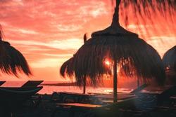 Straw beach umbrella at coral sunset