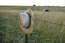 Straw cowboy hat on a barbed wire fence with a hay bale in the distance