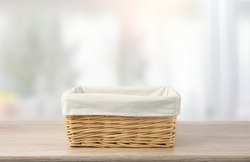 Straw empty basket decorated with white linen on wooden table,food advertisement template.Container.