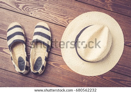ff33430830355 Straw hat and espadrilles on wooden background. Top view