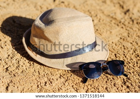 6ddcff0e71f7 Straw hat and sunglasses on sand beach.