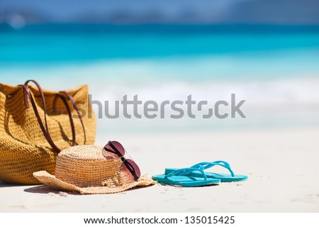 Straw hat, bag, sun glasses and flip flops on a tropical beach #135015425