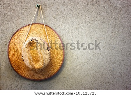 straw hat hang on a textured wall