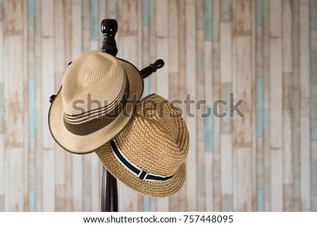 Straw hat hanging on wooden hanger.clothing accessories and travel concept