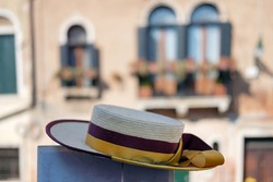 Straw hat of a gondolier with Venetian facade background, selective focus