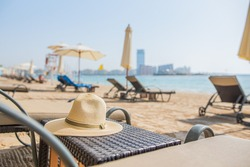 straw hat on a table next to a sun lounger on the beach with palm trees and sea views. rest at the resort, travel to hot countries