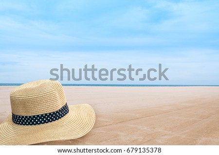 Straw hat on the shore of a beach,Woven fedora  hat on sand background. Vacation concept #679135378