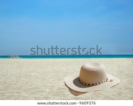 straw hat on the shore of a Caribbean beach - stock photo
