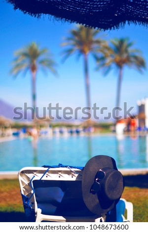 Straw hat, sun glasses on the lounger, near pool. At the background palm trees and mountains. The best rest, sunburn, sunny day, travel, paradise. First minut.