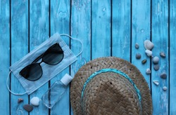 Straw hat, sunglasses, pebbles, medical mask and antiseptic on a wooden background. The tourist crisis in the summer of 2020 is associated with the epidemic of the Covid-19 coronavirus.