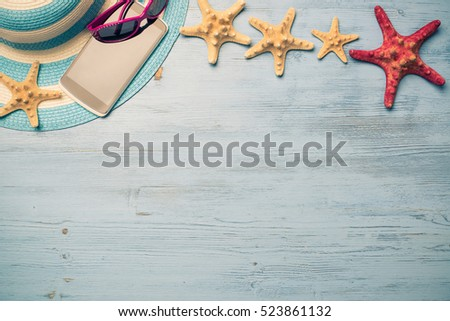 Straw hat sunglasses smartphone and photocamera among sea shells and stones on wooden surface - Shutterstock ID 523861132