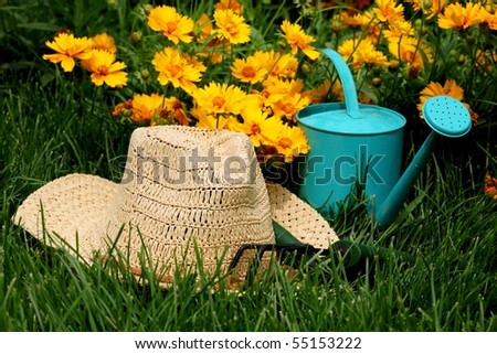 straw hat, watering pot and gardening tools in the garden