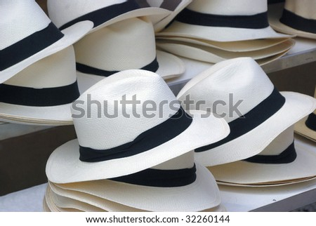 Straw hats with black band at a market. Focused at the first left down