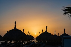 Straw parasols and palm trees silhouettes on the beach at sunset