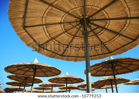straw parasols on beach on blue sky background