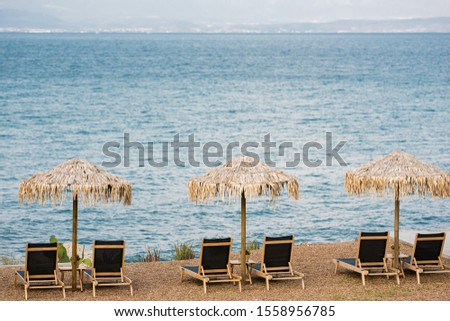 Straw sunshades and wooden sunbeds on an empty beach #1558956785