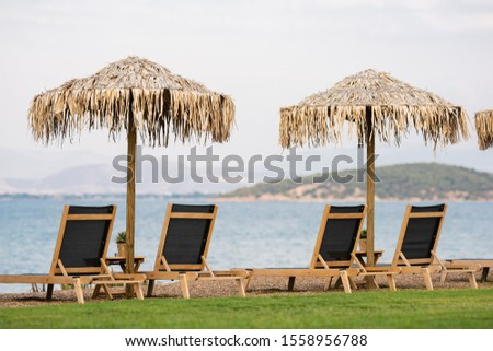 Straw sunshades and wooden sunbeds on an empty beach #1558956788