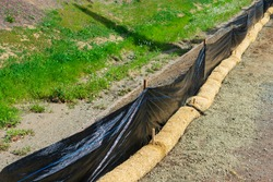 Straw wattles and plastic fence placed along dry waterway to reduce soil erosion, debris runoff and retain sediment during construction and maintenance project.