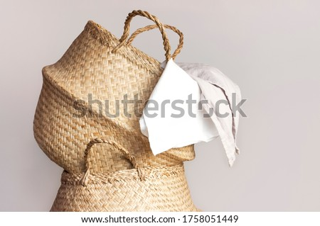Straw wicker basket and white natural cotton fabric, towel on gray background. Fashionable bamboo basket stylish interior item eco design handmade. Decor of home. Natural eco materials, storage basket