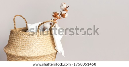 Straw wicker basket, natural cotton fabric, cotton flower branch on gray background. Bamboo basket stylish interior item eco design handmade. Decor of home. Natural eco materials, storage basket