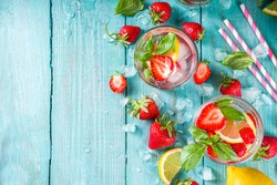 Strawberries and basil lemonade. Summer cold iced cocktail recipe, with fresh strawberry, lemon and basil leaves, wooden background copy space