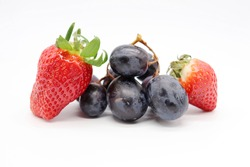 strawberries and blue grapes on white background