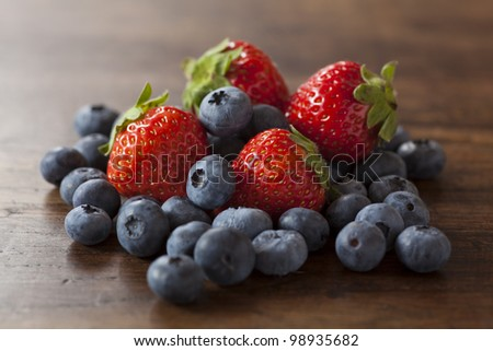 strawberries and blueberries on the wood table - stock photo