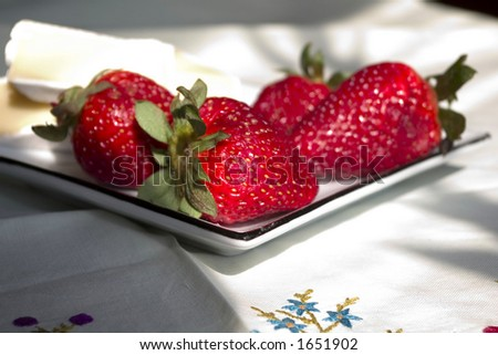 strawberries and cheese slices on table-cloth with embroidery