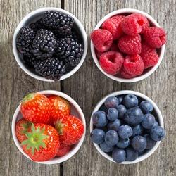 strawberries, blueberries, blackberries and raspberries in bowls, top view, close-up