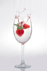 Strawberries fall into a glass of water on   a gray background with spray
