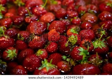 Strawberries glisten in a bath