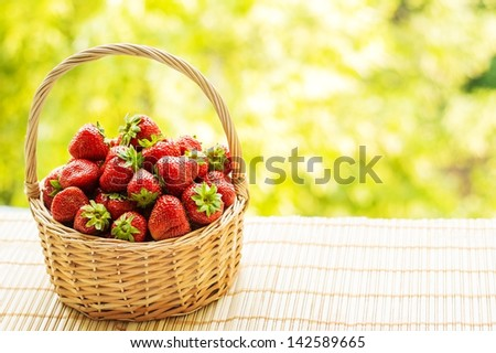 Strawberries in a basket on a green background. Strawberries in a basket. Garden, vegetable garden, fruit. Strawberry on the background of green.