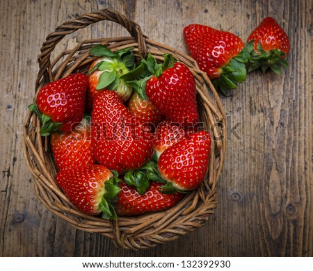 strawberries in a basket - wooden  background