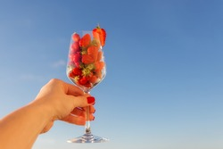 Strawberries in a glass of wine against a blue sky with a copy of space for prints, decor, wallpaper, posters. A glass of strawberries in a woman's hand.