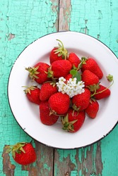 strawberries in a white plate on a wooden background