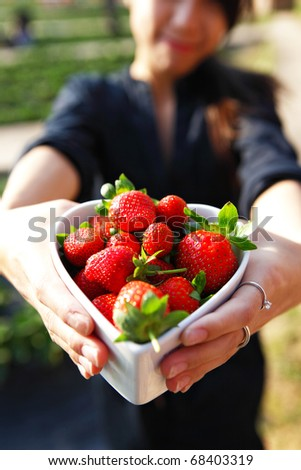 strawberries in heart shape bowl show by girl