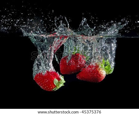 strawberries in water with bubbles on black ground