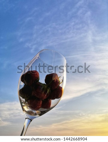 Strawberries in wineglass on sky background  #1442668904
