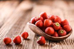 Strawberries in wooden bowl. Fresh nice strawberries on wooden table. Juice strawberry