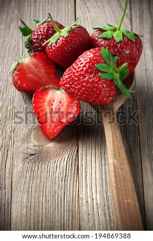 Strawberries in wooden spoon on weathered wood.