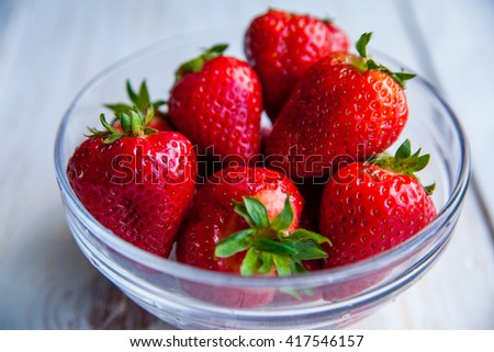 Strawberries on the plate on white wooden background for breakfast