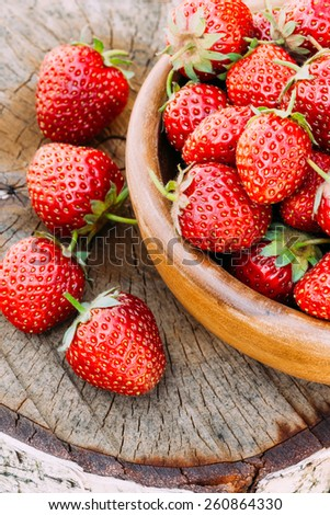Strawberries. Organic Berries Closeup. Ripe Strawberry In The Fruit Garden, Old Wooden Bowl Filled With Succulent Juicy Fresh Ripe Red Strawberries On An Old Birch Stump. Toned Instant Image