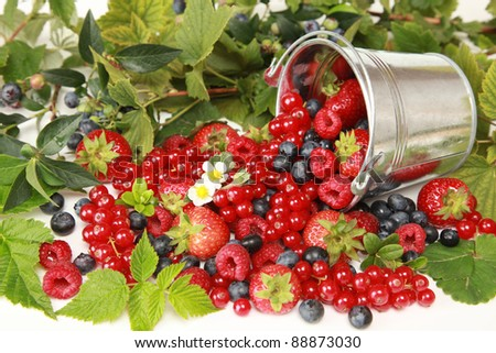 Strawberries, red currants, raspberries and blueberries on white falling out of a bucket