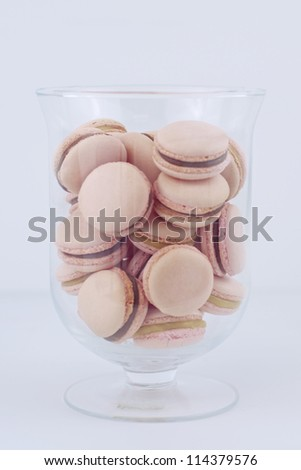 Strawberry & caramel and chocolate macrons in a glass jar - stock photo