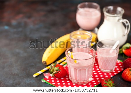 Stock Photo Strawberry and Banana Smoothie or Milkshake with a Straw in a Glass with fresh Berries on dark background. Healthy food for breakfast and snack. Selective focus.