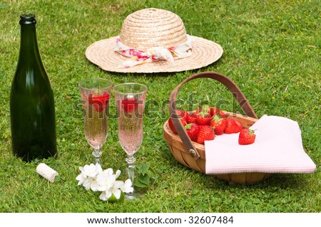 Strawberry and champagne picnic with basket of fruit